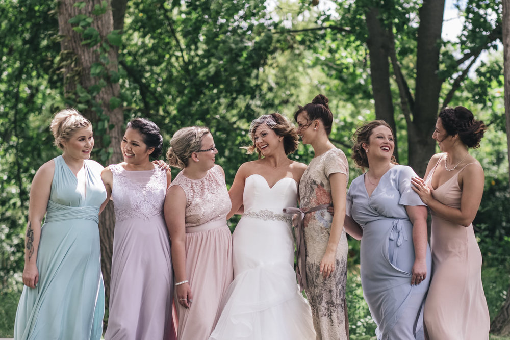 Bride and her bridesmaids in beautiful pastel dresses.
