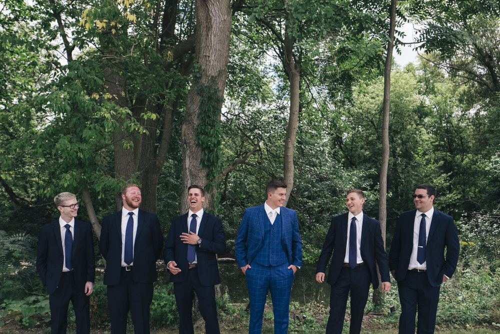 Groom in striped blue suit with groomsmen.