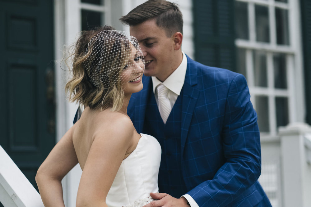 Bride in birdcage veil and groom in striped blue suit.