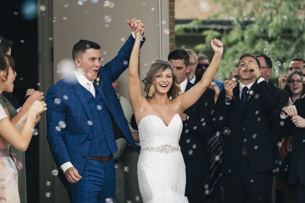 Bride and groom do grand exit to bubbles after wedding ceremony.