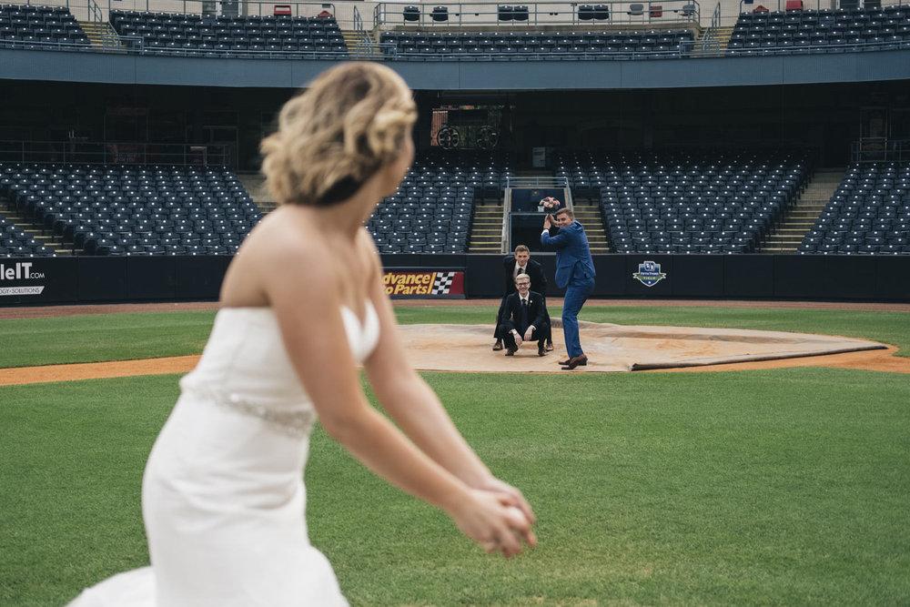 Bride pitches to husband on wedding day at Toledo Mudhens Stadium.