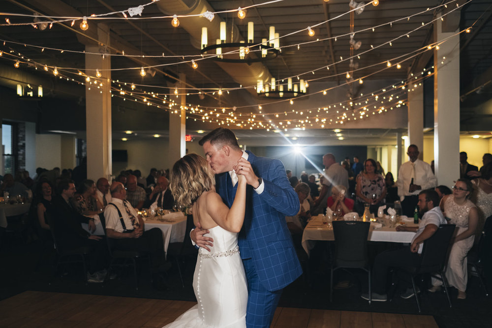 Bride and groom dance under string lights at their Hensville wedding reception.