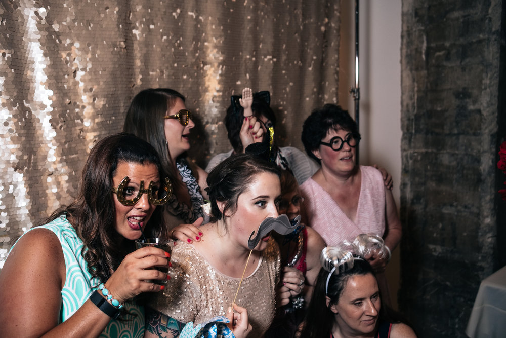 Bride gets in the photobooth with friends during her wedding reception in Toledo, Ohio after her destination wedding in Hawaii.