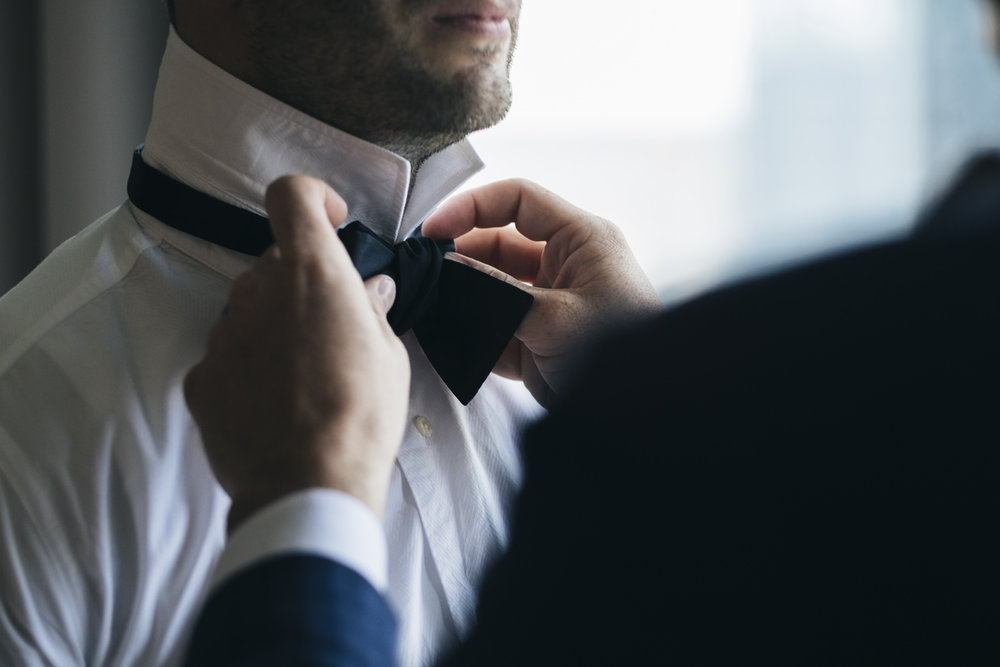 Best man fixes the groom's bowtie during styled shoot at the Renaissance Hotel.
