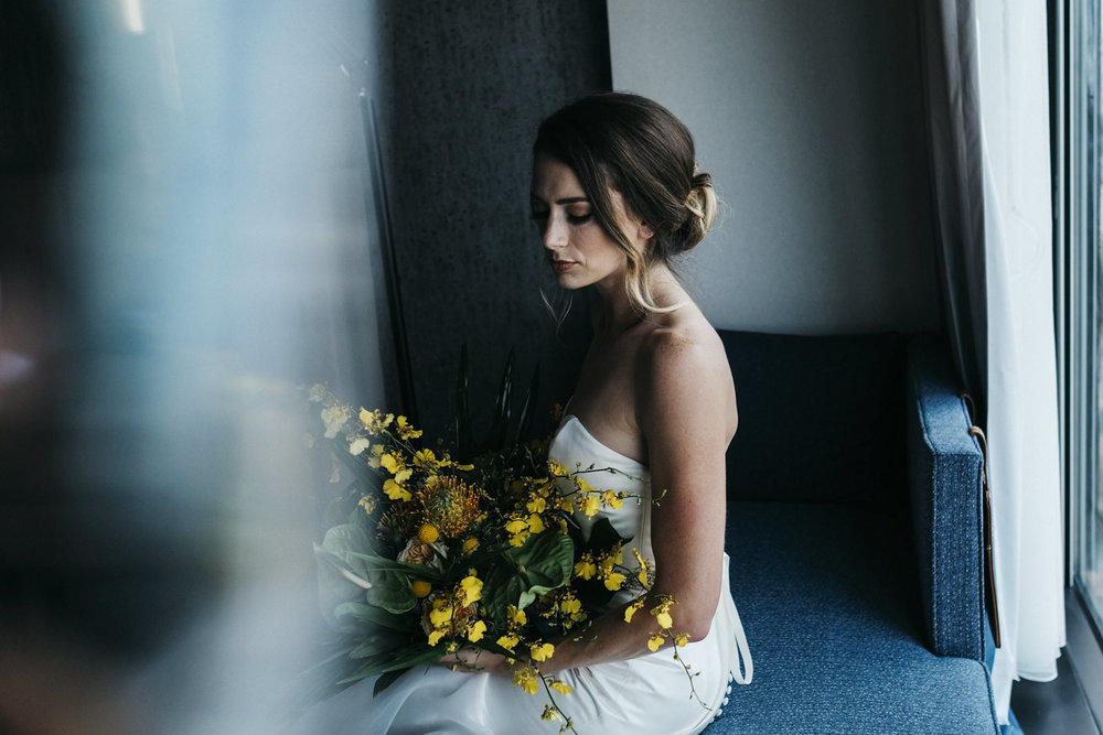 Bride sits with her Urban Flowers yellow bouquet in a hotel room in Northwest, Ohio.