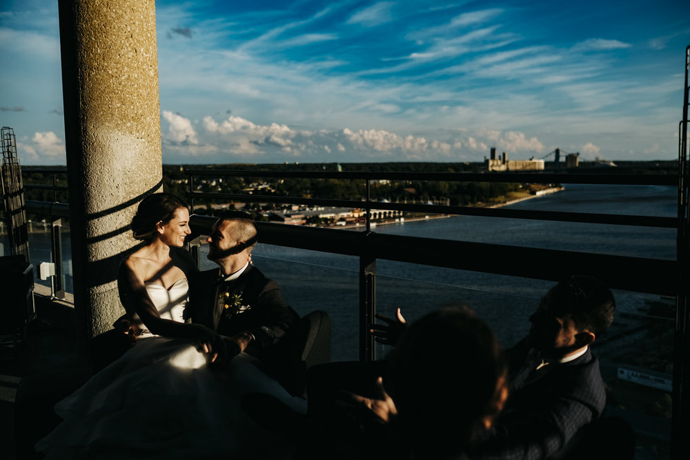 Bride and groom sit with their friends on a rooftop in Toledo, Ohio.