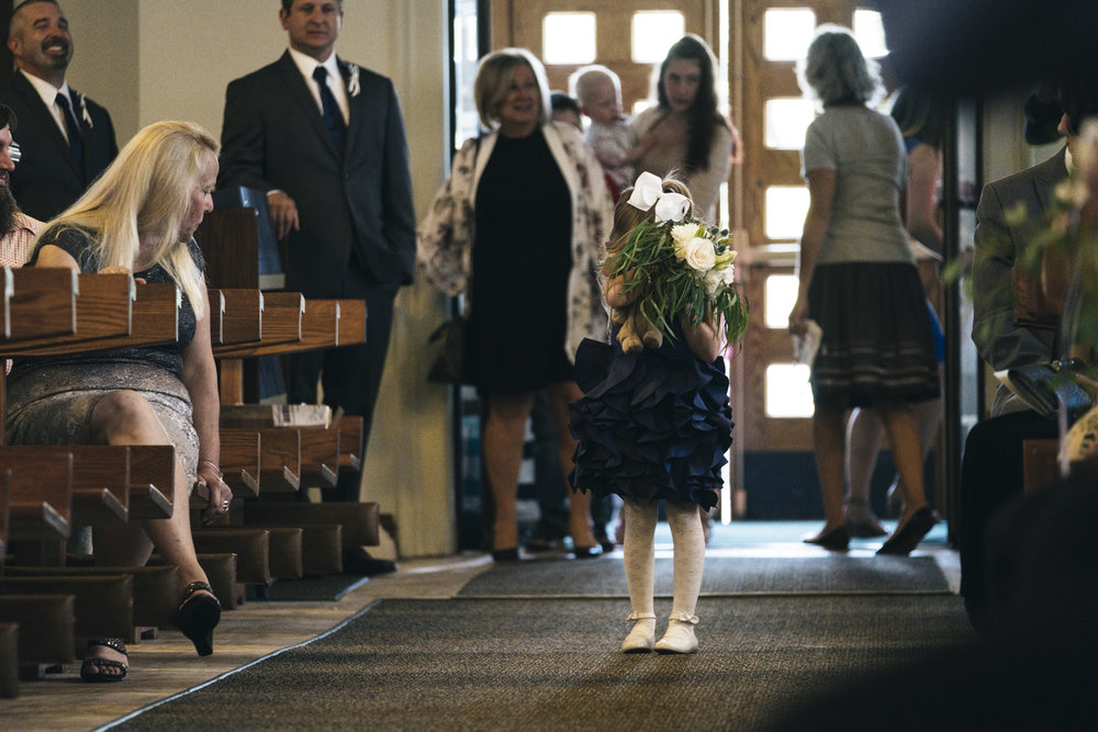 The flower girl covers her face in embarrassment while walking down the aisle at a wedding in Michigan.