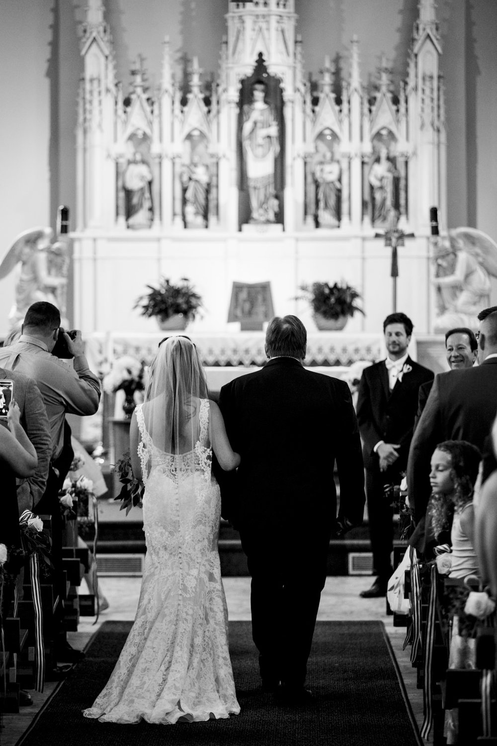 The father of the bride walks his daughter down the aisle on her wedding day in Michigan.