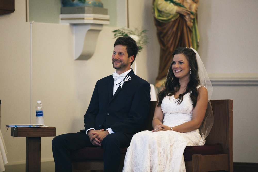 The bride and groom sit during their Catholic wedding ceremony in Michigan.