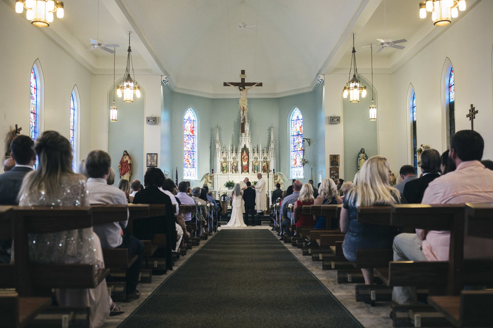 The bride and groom stand at the alter of a Catholic wedding ceremony.