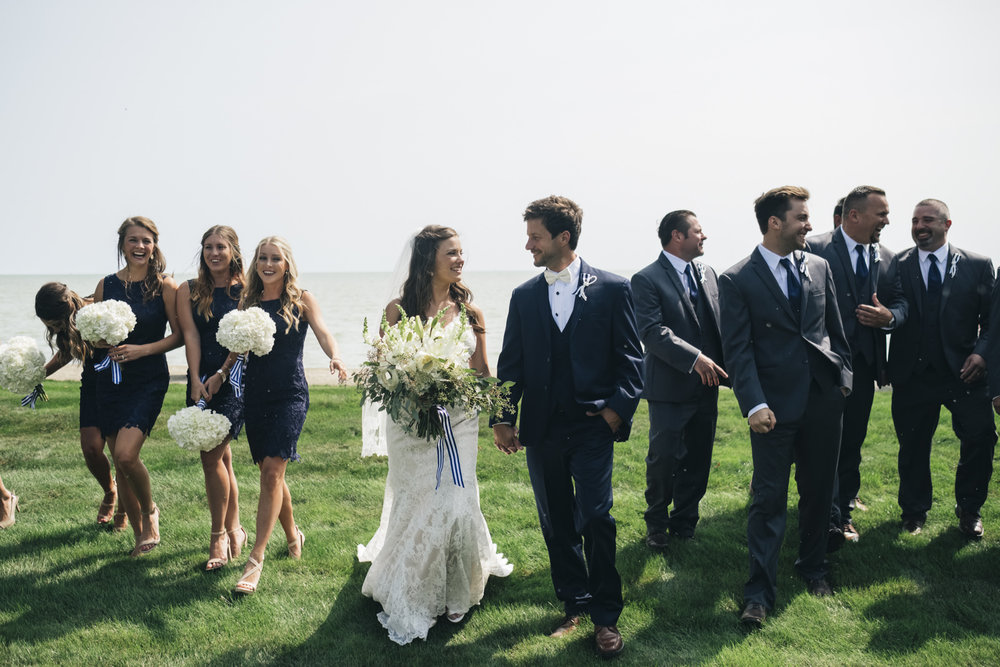 The bridal party walks near the lake at a nautical themed wedding in Michigan.