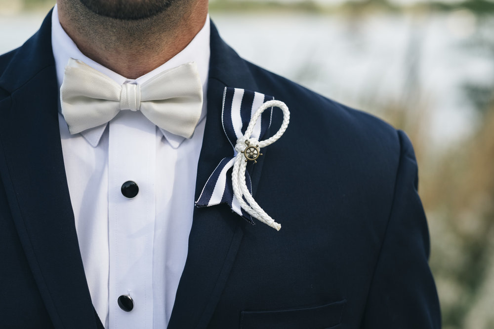 Navy and white boutonniere completely with a little ship steering wheel!