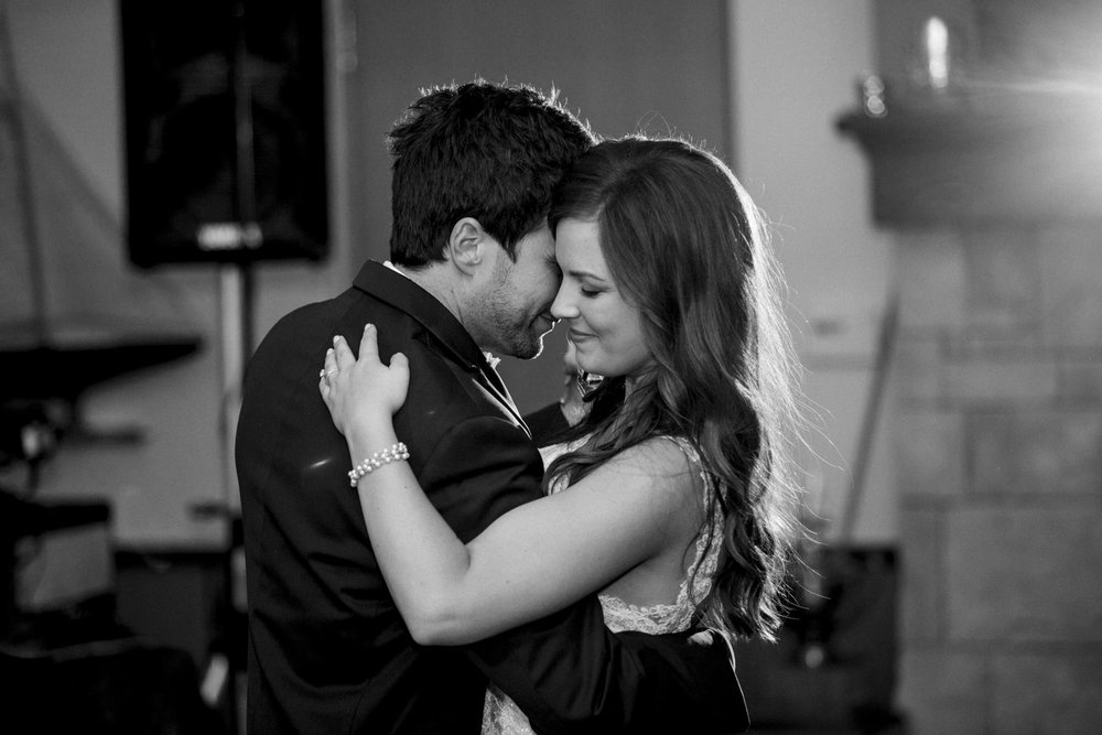 Bride and groom dance during their wedding reception in a black and white photograph.
