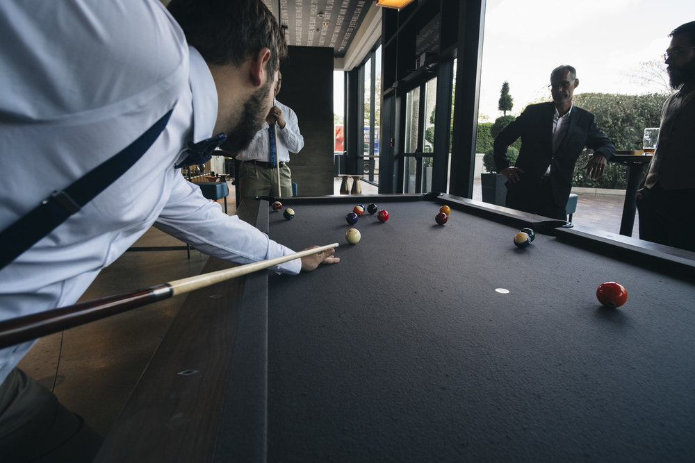 Groom and his groomsmen playing pool in the lobby at the hotel.