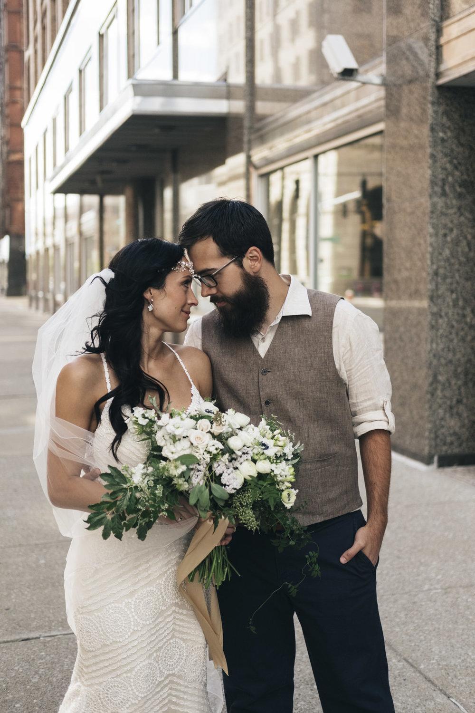 Bride and groom portrait with beautiful Bartz Viviano floral arrangement.