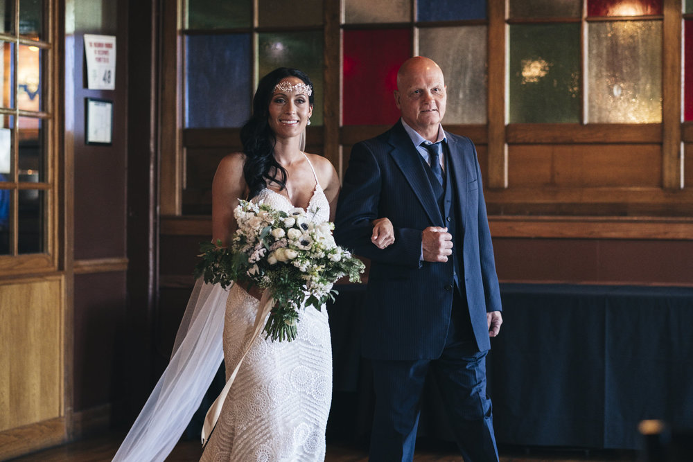 Bride walks down the aisle with her father at Oliver House wedding.