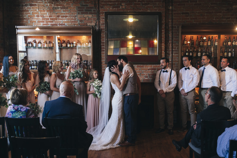 First kiss during intimate wedding ceremony in The Oliver House.