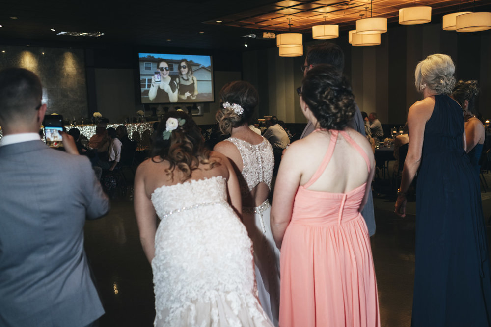 Bridal party watches a video made by the bridal party.