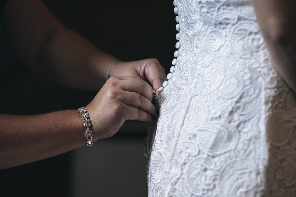 The bride has her wedding dress from Fantastical Finds, Michigan, buttoned up by her mom in Toledo, Ohio.