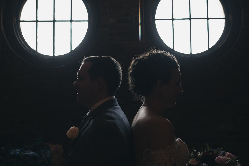 Bride and groom silhouetted in front of windows.