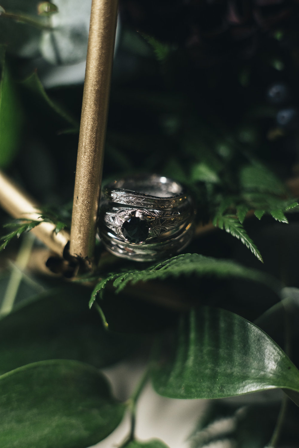 Wedding ring sits in geometric structure on table at wedding reception