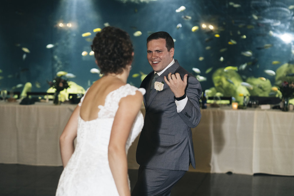 Bride and groom share their first dance in front of a beautiful, large fish aquarium