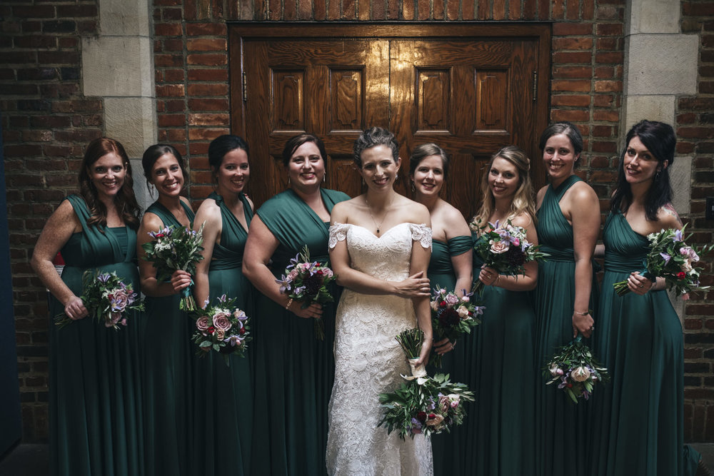Bride poses with bridesmaids wearing green with their bouquets from Bartz Viviano.