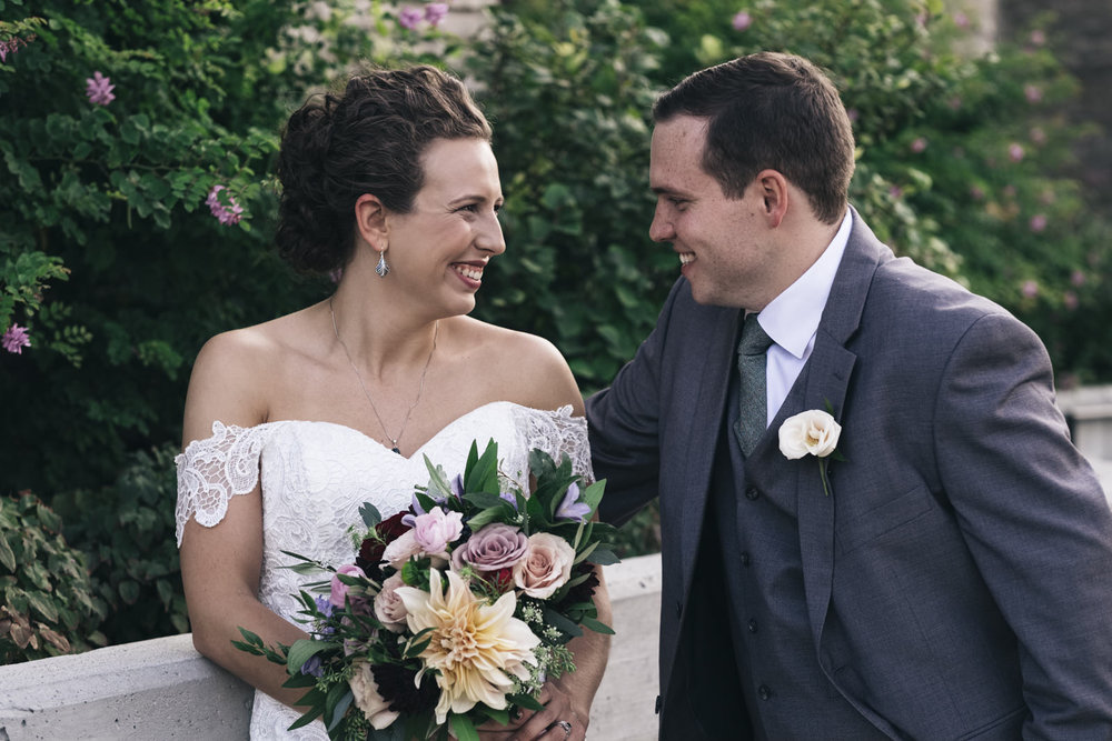 Bride wears an off-shoulder dress and has a curly updo for her wedding in September.