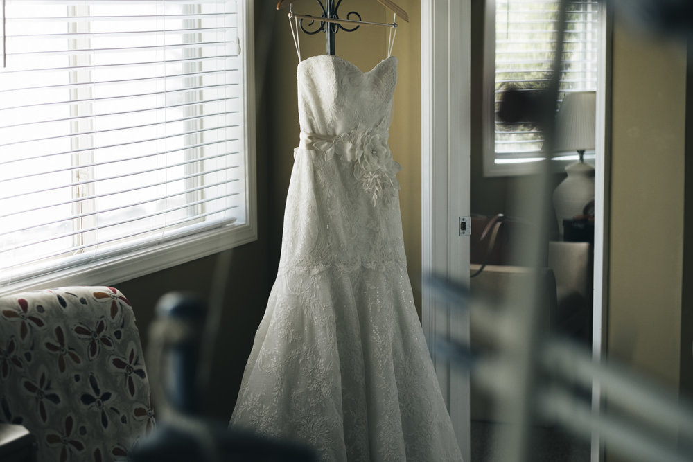 Dress White of Dublin hangs in the doorway before nautical themed wedding