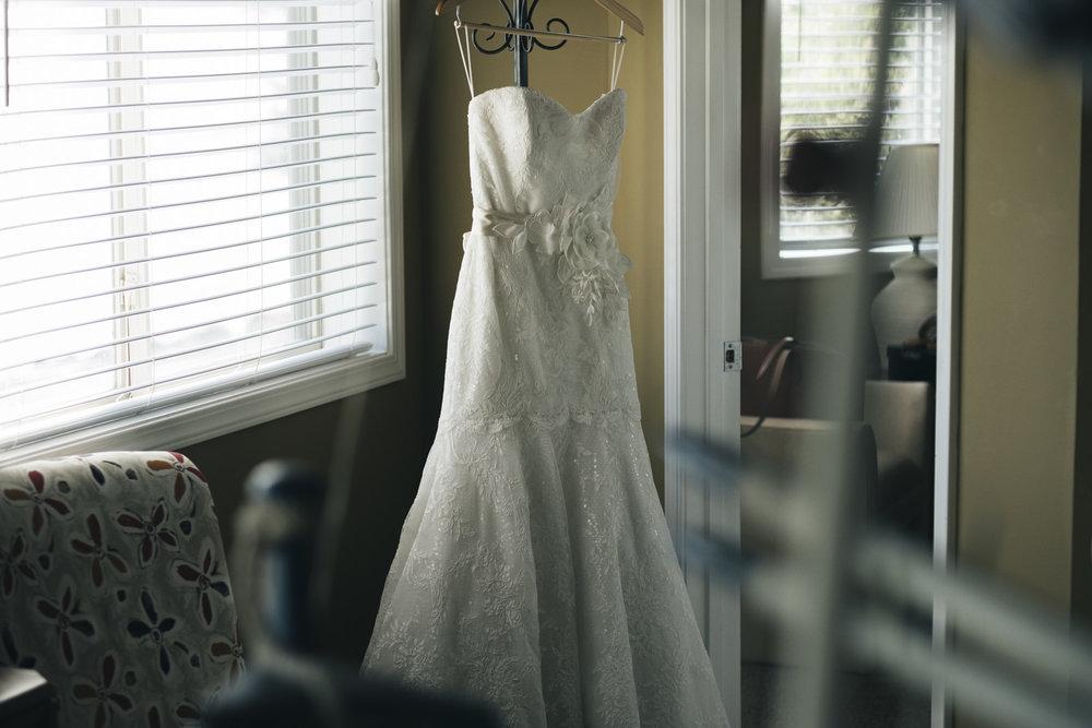 Dress White of Dublin hangs in the doorway before nautical themed wedding