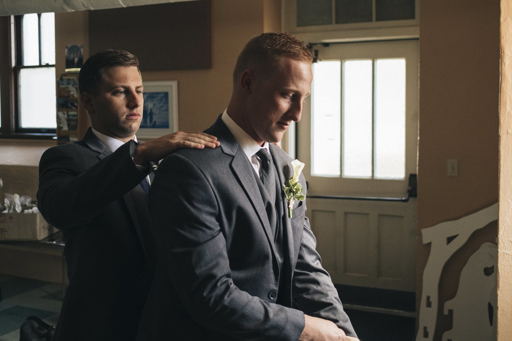 Best man helps the groom get ready before his wedding ceremony near lake Erie.
