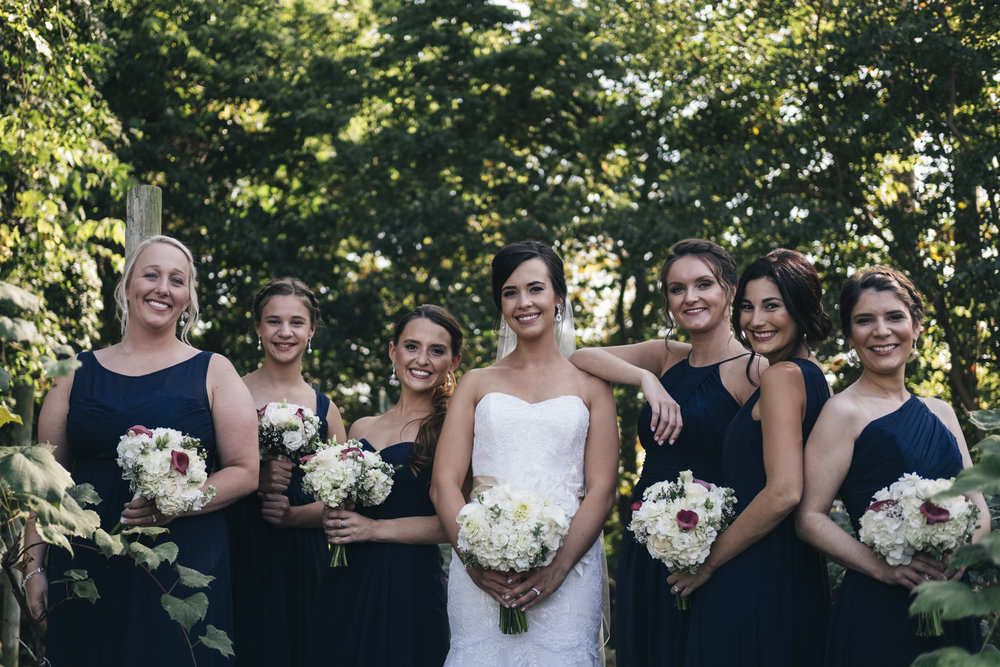 Bridesmaids stand around the bride and smile in their navy blue dresses outside for late summer wedding in Northern Ohio.