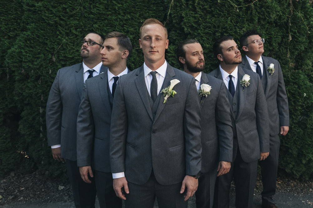 Groomsmen stand around the groom for a picture with Toledo wedding photographers in Marblehead, Ohio.