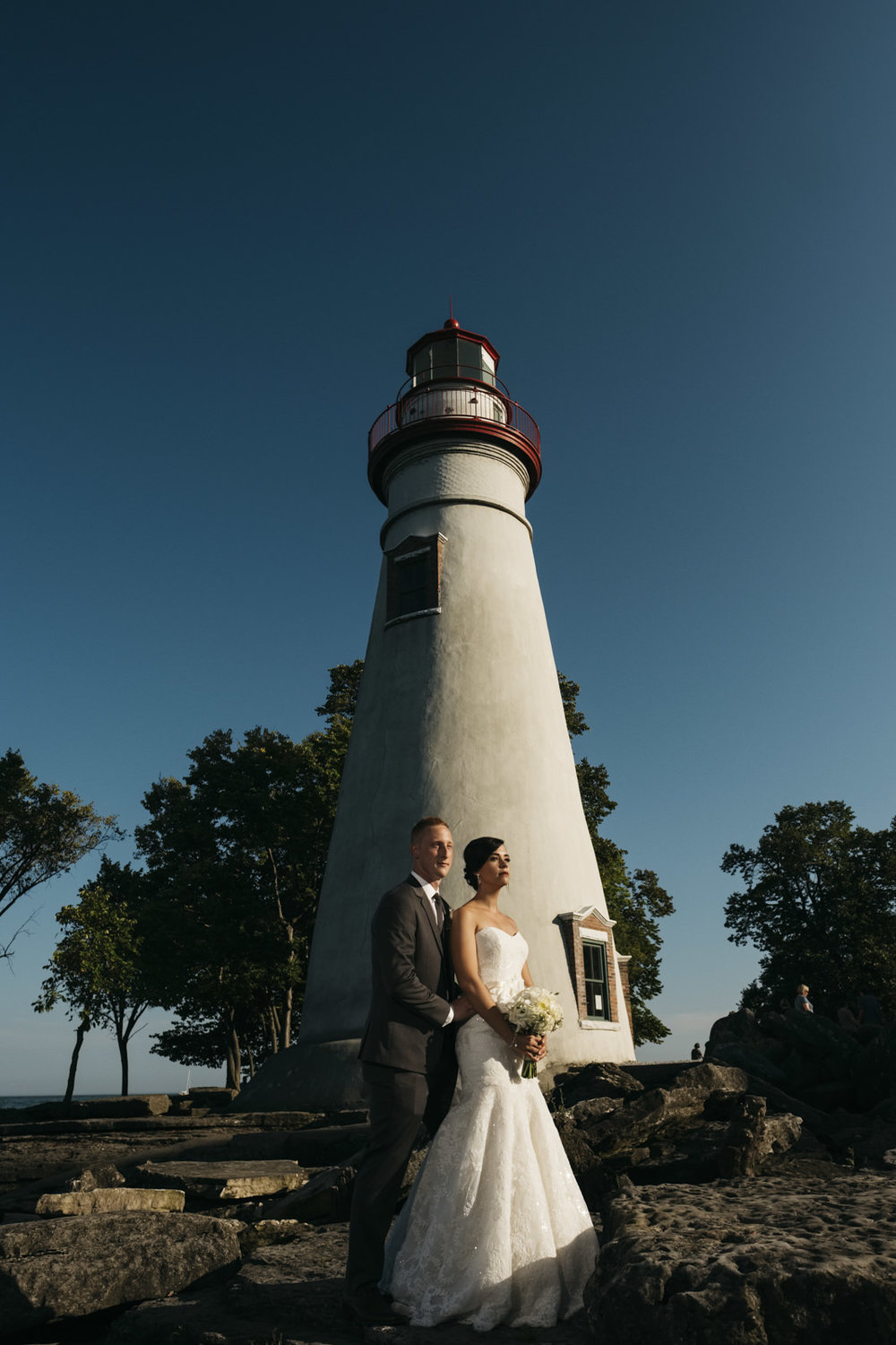 bride and groom stand for a portrait near a lighthouse in Northern Ohio on the shores of Lake Erie.