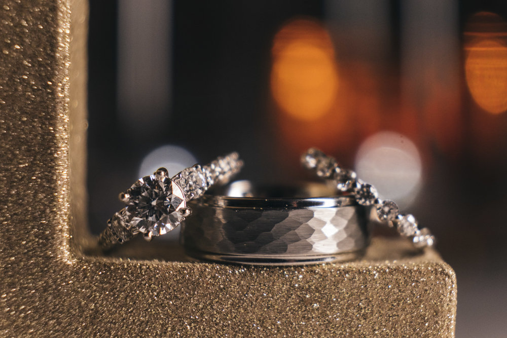 Gold and silver wedding rings sit on a sparkly golden ledge during wedding reception