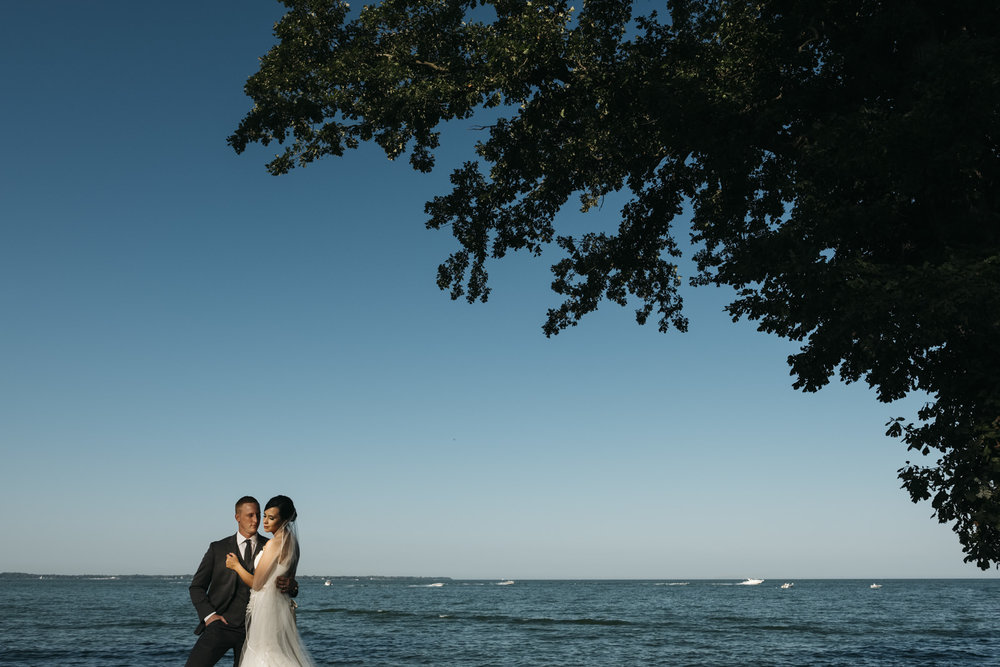 Bride an groom stand on the shore of Lake Erie for their bridal portrait session in Marblehead, Ohio.