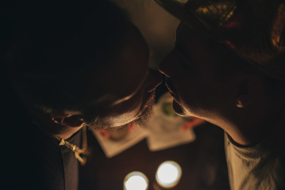 Cute same-sex couple kisses at The Owl bar in Chicago, Illinois