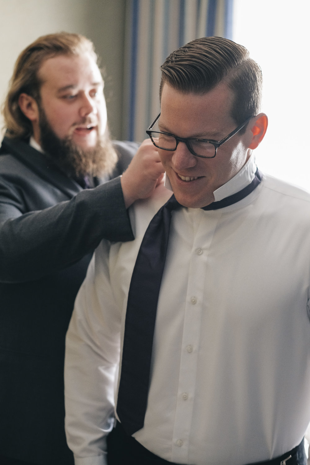 Best man helps groom get ready before his wedding ceremony in Port Clinton, Ohio near Lake Erie