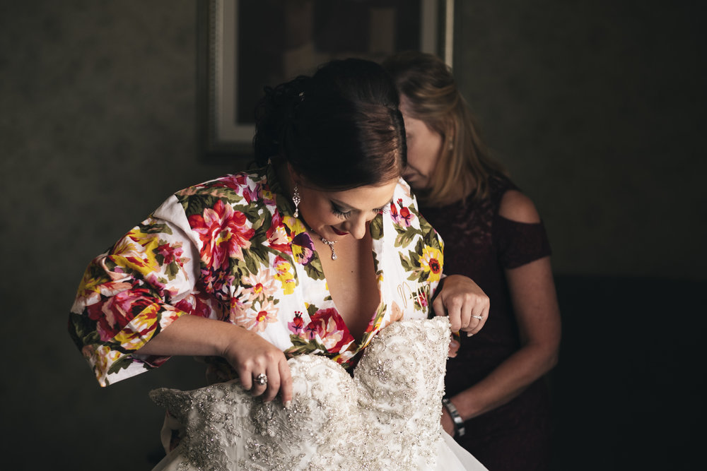Bride steps into her fluffy Belle Amour dress before her Lake Chautauqua wedding