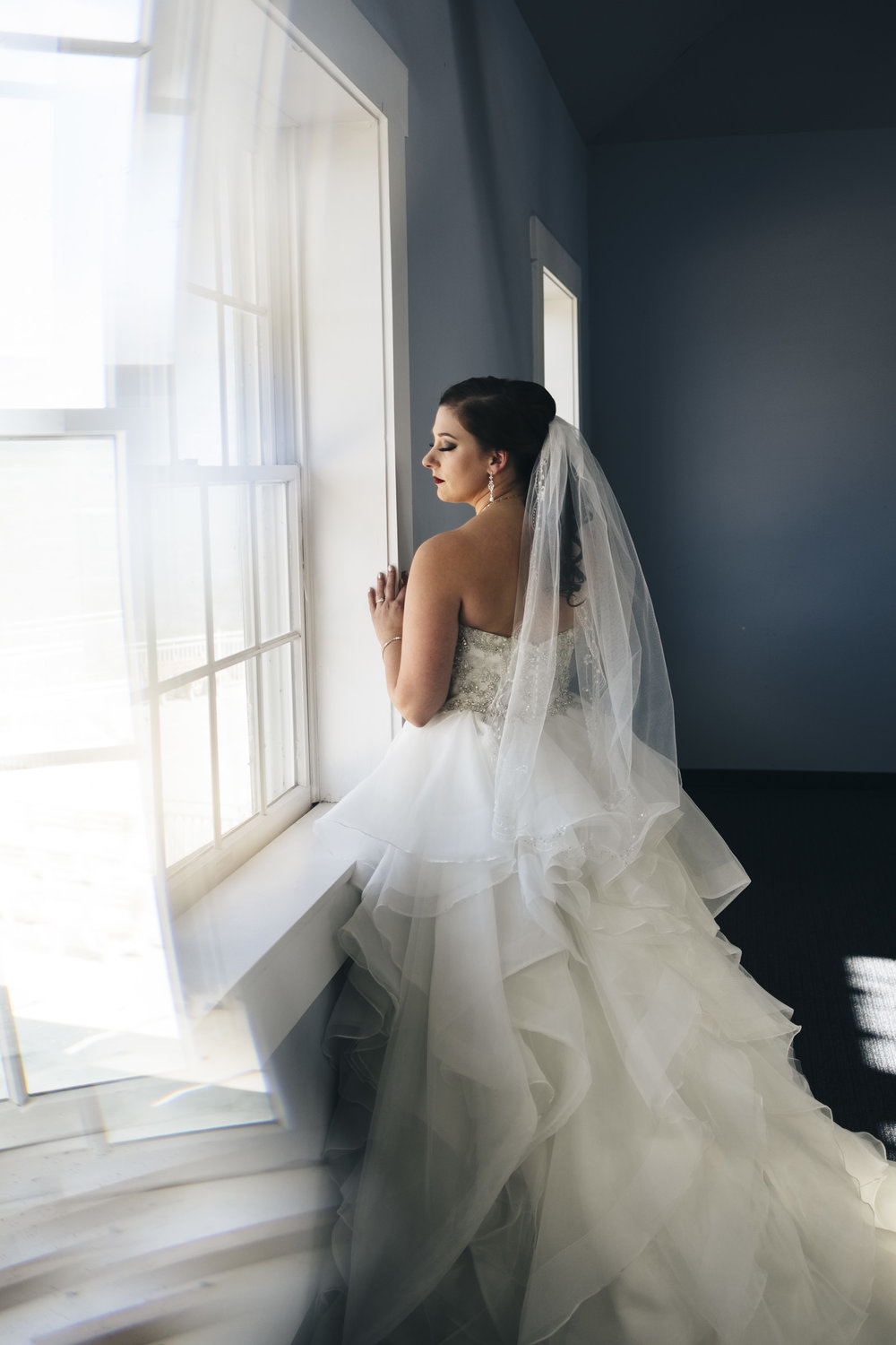Bride stands near a window overlooking Lake Erie for her early fall wedding