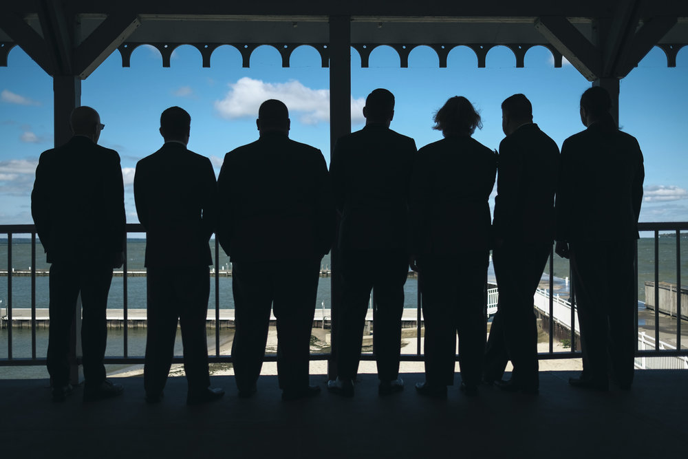 Groom and groomsmen stand on a balcony overlooking Lake Erie in early October