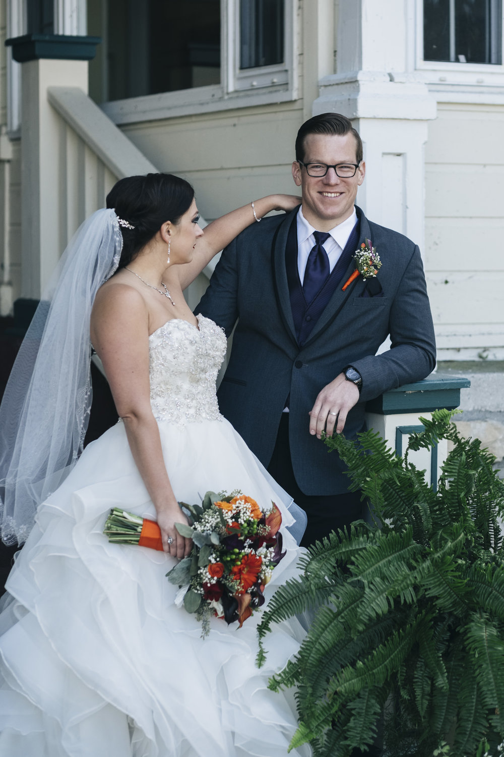 Bride stands with her groom in Chautauqua with her orange and purple floral bouquet