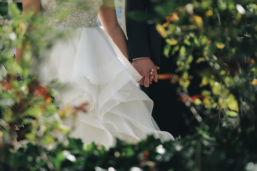 Bride and groom hold hands in garden outside of hotel near Port Clinton, Ohio