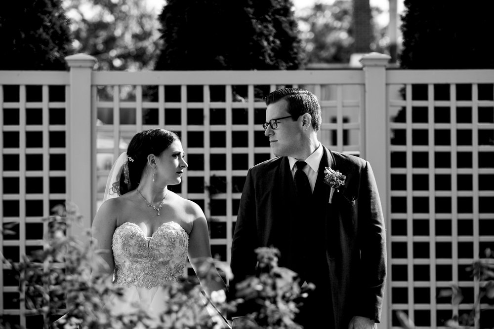 Black and white photo of bride and groom in a garden for their wedding day creative session