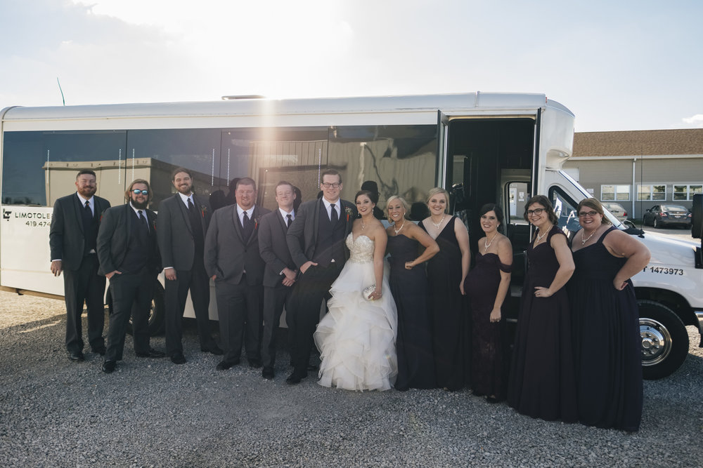 Bridal party stands outside of party bus before heading to the wedding reception