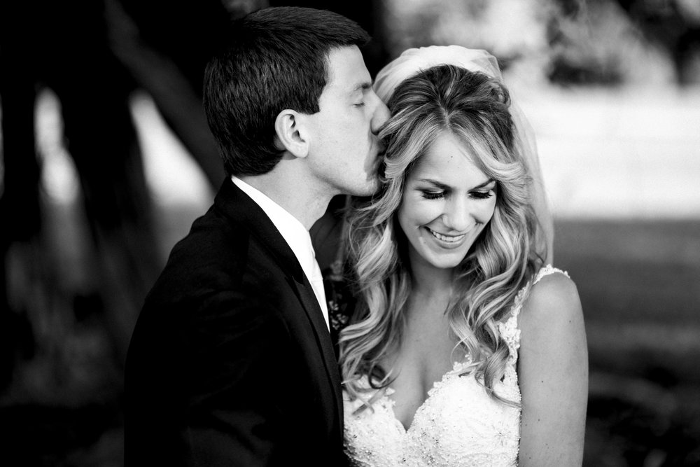 Groom kisses bride on the head in creative session on their wedding day, black and white