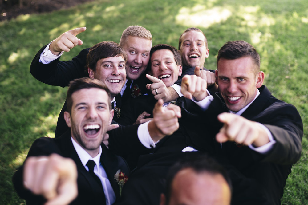 Groomsmen carry the groom and laugh in funny picture before the wedding ceremony