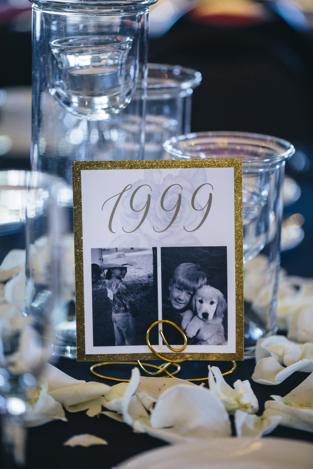 Table centerpieces with years and pictures of the bride and groom throughout their childhood