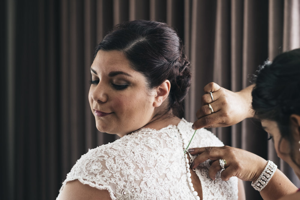 Bride gets her dress buttoned up with help from her mom in this intimate wedding picture