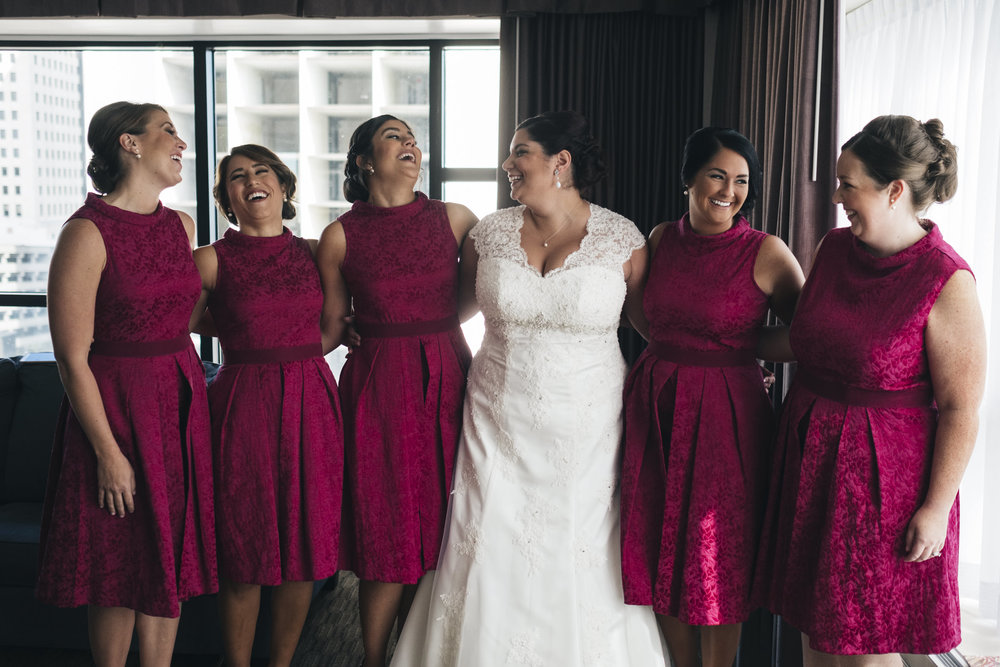 The bride stands around her bridesmaids in the hotel room at The Park Inn with her bridesmaids wearing bright pink dresses.